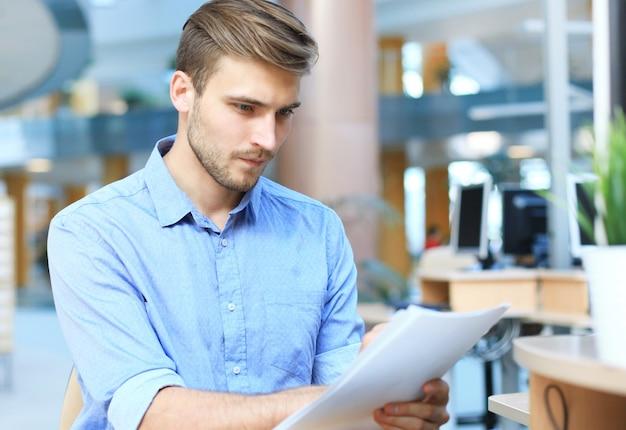 사무실 책상에서 서류를 읽는 젊은 사업가