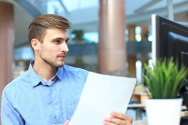 Young businessman reading paperwork at desk in office