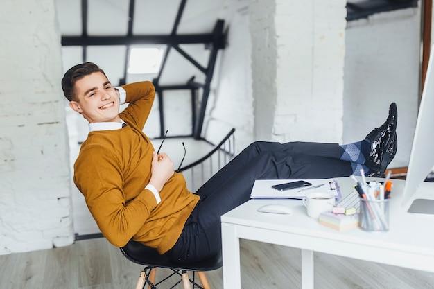 休憩中に彼のオフィスで休んでいる青年実業家