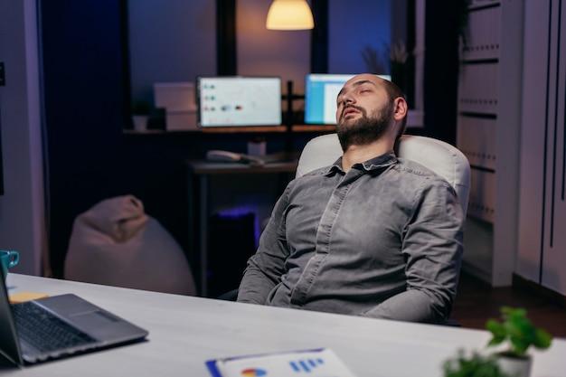 마감일에 일하는 동안 의자에서 쉬고 있는 젊은 사업가. 워커홀릭 직원은 중요한 회사 프로젝트를 위해 사무실에서 밤늦게 혼자 일하다 잠들었습니다.