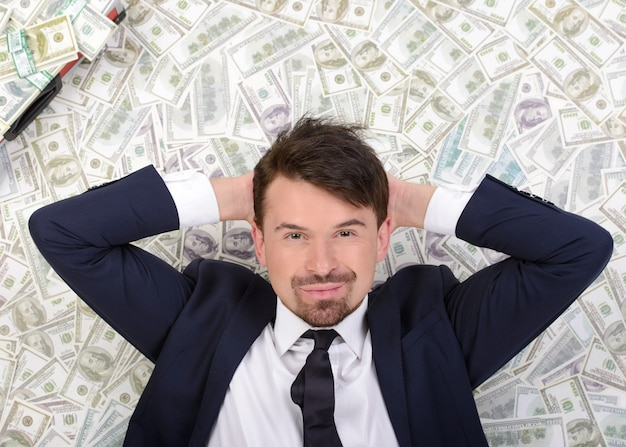 Young businessman resting upon money