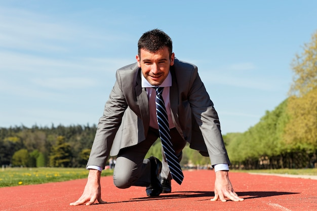 Young businessman on a running track in summer
