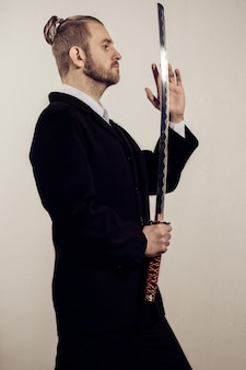 Молодой бизнесмен-самурай в черном костюме с японским мечом