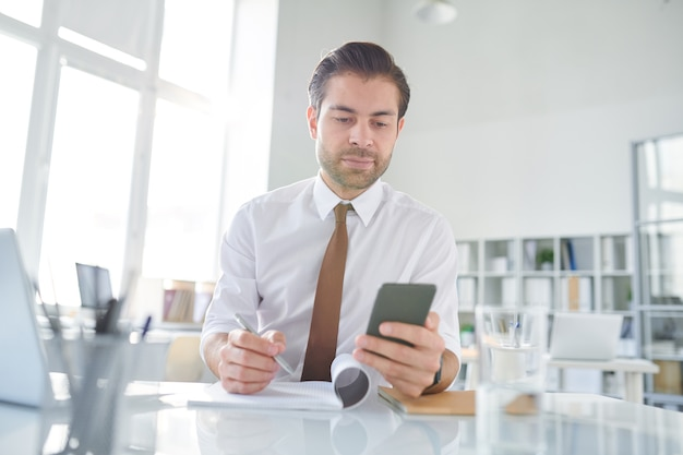 Young businessman scrolling in smartphone through business texts and writing down some new ideas