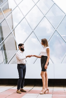 Young businessman shaking hand with businesswoman in front of modern building