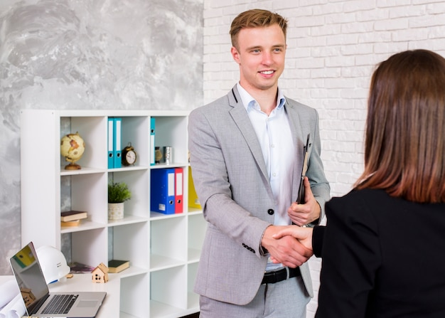 Young businessman shaking a woman hand