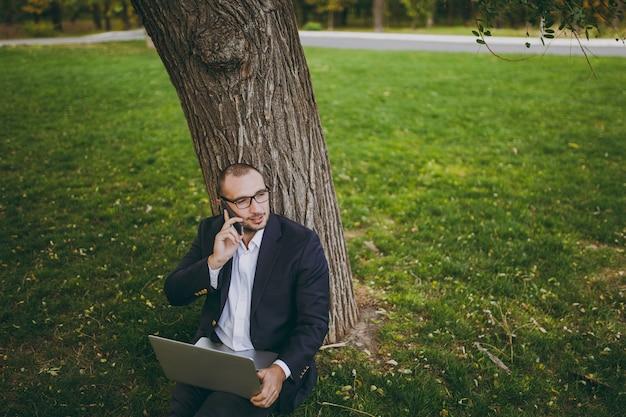 Giovane uomo d'affari in camicia, vestito, occhiali. l'uomo si siede sul terreno erboso, parla al telefono cellulare, lavora al computer portatile nel parco cittadino sul prato verde all'aperto sulla natura. ufficio mobile, concetto di affari.