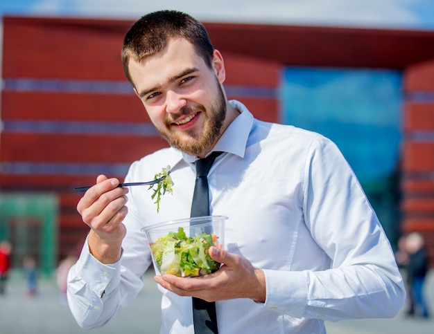 Young businessman in shirt and tie with salad lunch box