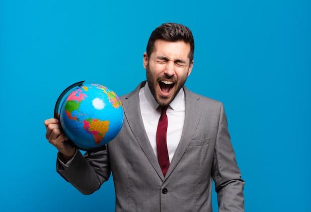 若いビジネスマンは積極的に叫び、非常に怒っている、イライラしている、憤慨している、またはイライラしているように見え、世界の地球地図を持っていないことを叫んでいます
