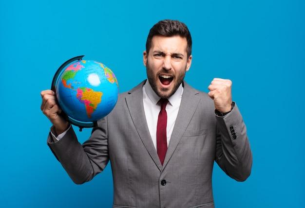 화난 표정으로 또는 주먹으로 공격적으로 외치는 젊은 사업가 세계 세계지도를 들고 성공을 축하합니다.