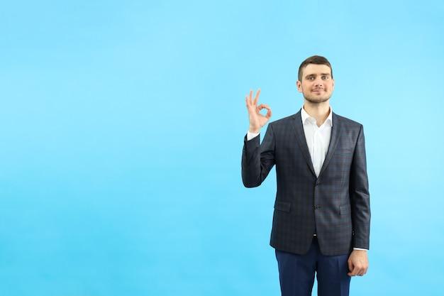 Молодой бизнесмен показывает знак ок на синем фоне.