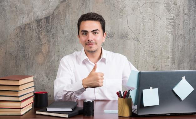 Молодой бизнесмен показывает палец вверх за офисным столом.