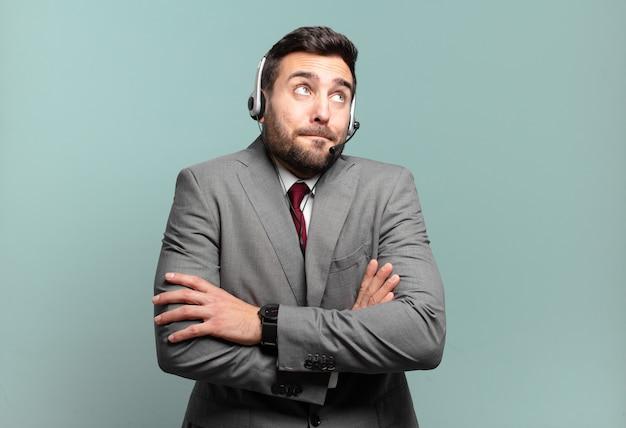 Молодой бизнесмен пожимает плечами, чувствуя себя смущенным и неуверенным, сомневаясь со скрещенными руками и озадаченно глядя на концепцию телемаркетинга