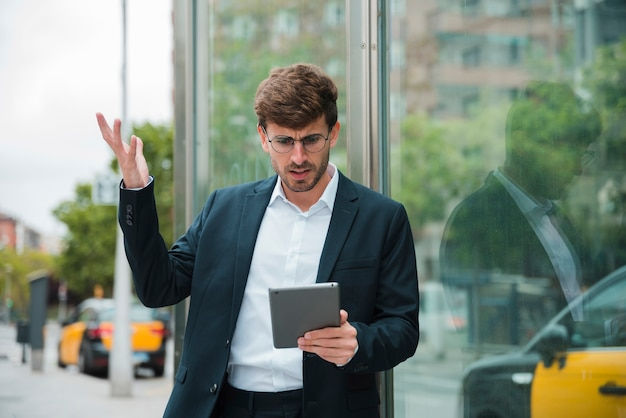 Young businessman shrugging while looking at digital tablet