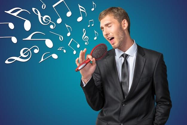 Молодой предприниматель поет, как будто в микрофон