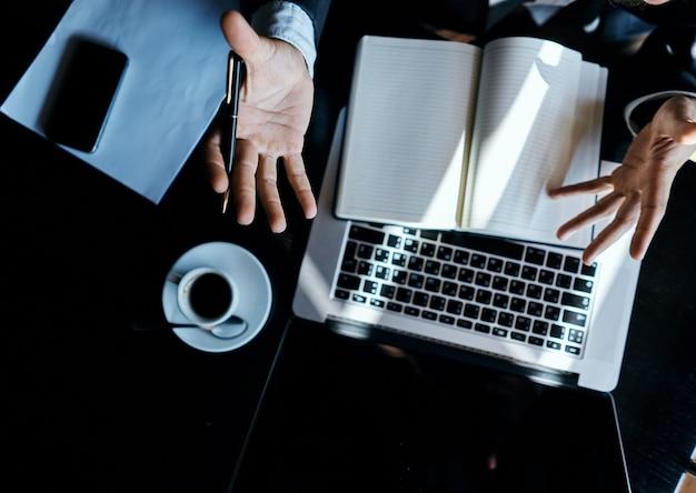 Молодой бизнесмен сидит за столом с бумагами и ноутбуком