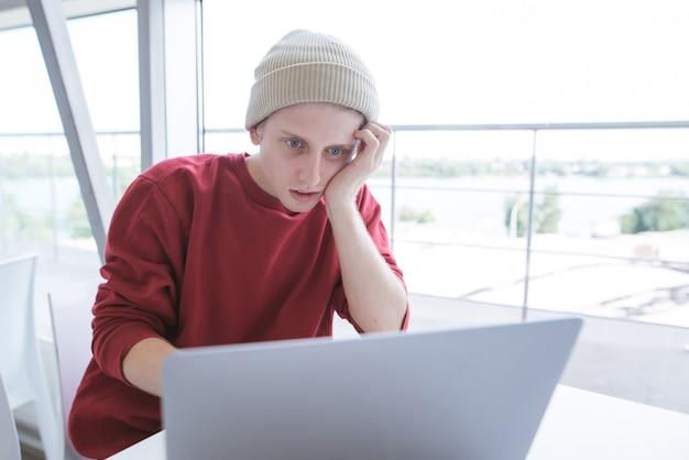 Молодой бизнесмен сидит у окна работает на ноутбуке и выглядит сосредоточенным на экране