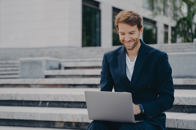 Young businessman sits on steps uses laptop organizes meeting online with investors