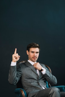 Young businessman sitting in armchair showing hand with one finger up