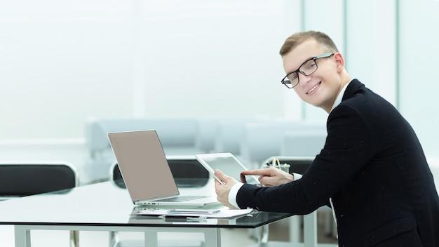 Молодой предприниматель, сидя за офисным столом