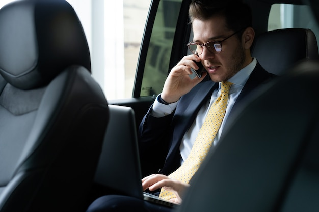 Young businessman sitting on back seat of the car, while his chauffeur is driving automobile