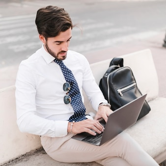 Young businessman sitting on bench working on laptop