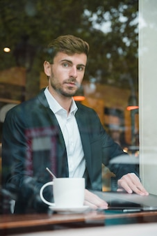 Young businessman sitting in the cafe with laptop