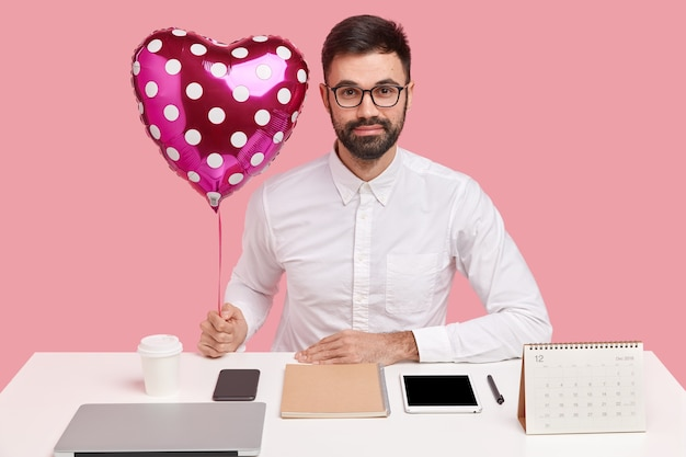 Young businessman sitting at desk with gadgets and holding heart-shaped balloon