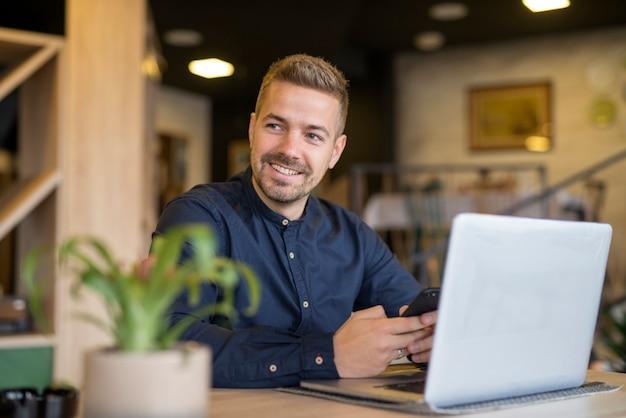 Молодой бизнесмен сидит в уютном кафе-баре с помощью портативного компьютера и смотрит в сторону