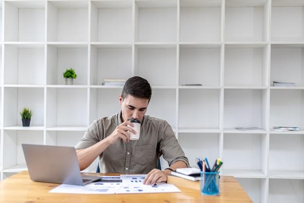 ラップトップを持ってオフィスに座って、書類をチェックしながらホットコーヒーを飲みながら、スタートアップを設立した若いビジネスマンは、成長する会社を経営するスキルを持った若い起業家です。