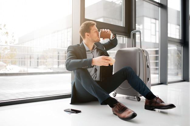 바닥과 음료 커피에 앉아 젊은 사업가