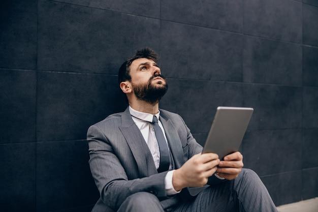 路上に座って、タブレットを押しながら問題を抱えている青年実業家。