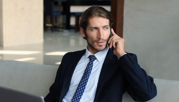 ホテルのロビーのソファに座って電話をかけ、誰かを待っている青年実業家。