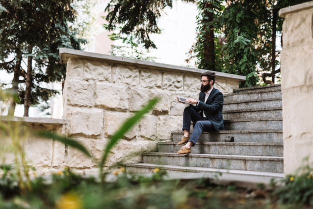 Young businessman sitting on staircase using laptop at park