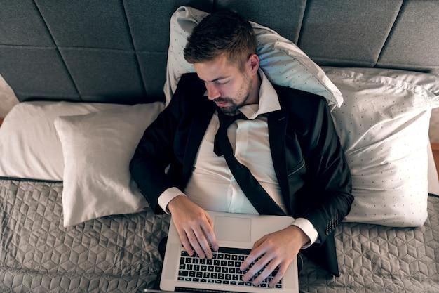 ラップトップが付いているベッドで寝ている青年実業家。キーボードの手。過労の概念。