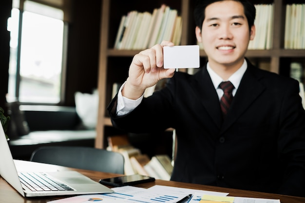 Young businessman smile and holding blank business card in office, business concept