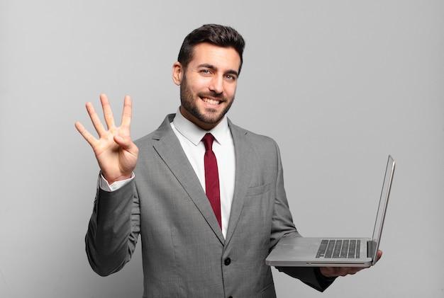 Молодой бизнесмен улыбается и выглядит дружелюбно, показывает номер четыре или четвертый с рукой вперед, считает и держит ноутбук