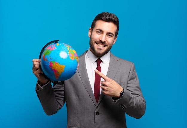 젊은 사업가 유쾌하게 웃고, 행복감을 느끼고 측면과 위쪽을 가리키는, 세계 세계지도를 들고 복사 공간에 개체를 표시
