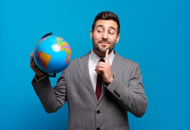 행복 하 게 웃 고 공상 또는 의심 젊은 사업가 세계 세계지도를 들고 측면을 찾고