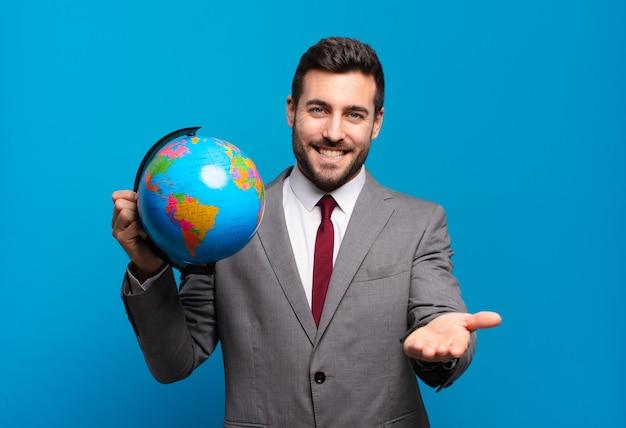 친절하고 자신감 있고 긍정적 인 표정으로 행복하게 웃고, 세계 세계지도를 들고 물건이나 개념을 제공하고 보여주는 젊은 사업가