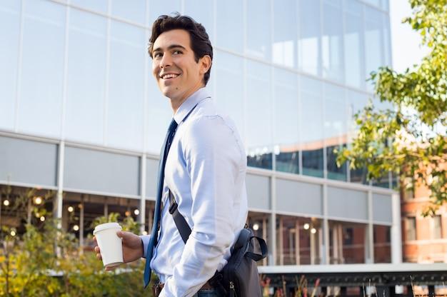 Молодой предприниматель улыбается на открытом воздухе в городе