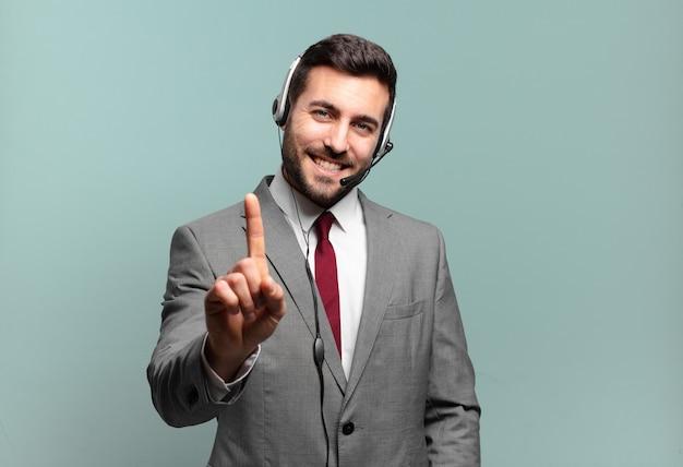 誇らしげに微笑む若いビジネスマンが、自信を持ってナンバーワンのポーズをとり、リーダーのテレマーケティングのコンセプトのように感じている