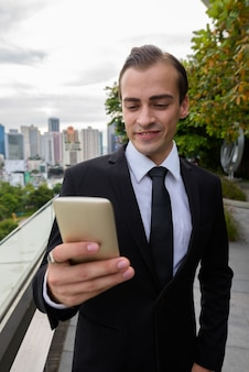 Young businessman smiling and using mobile phone