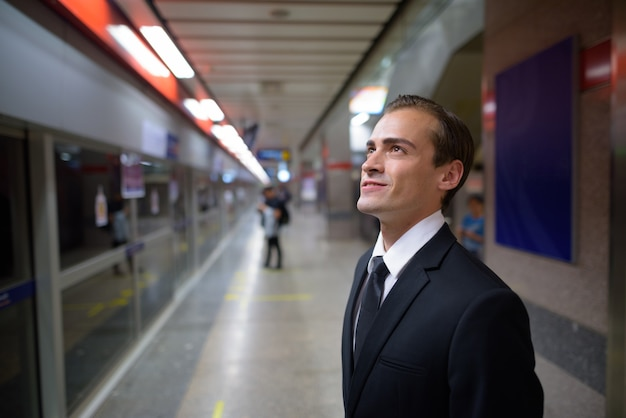 Young businessman smiling and waiting train at platform