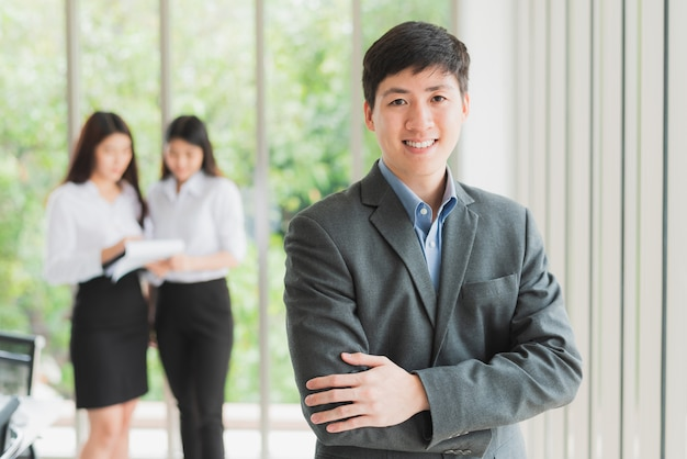 Young businessman smiling with arms crossed