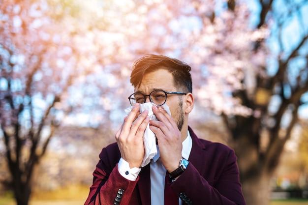 공원에서 재채기 하는 젊은 사업가. 알레르기, 독감, 바이러스 개념.