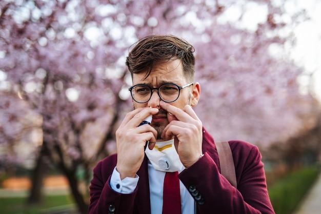 공원에서 재채기를 하고 코를 사용하는 젊은 사업가. 알레르기, 독감, 바이러스 개념.