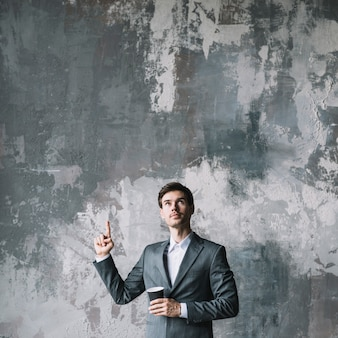 Young businessman standing against concrete wall pointing his finger upward looking up