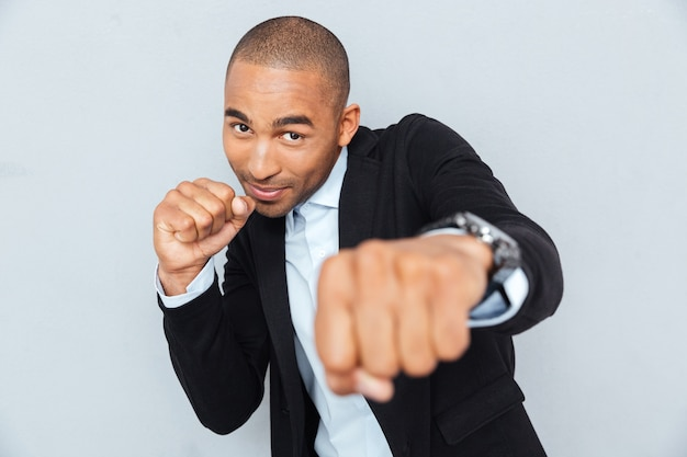 Young businessman standing in boxer position and ready to fight clenching his fists