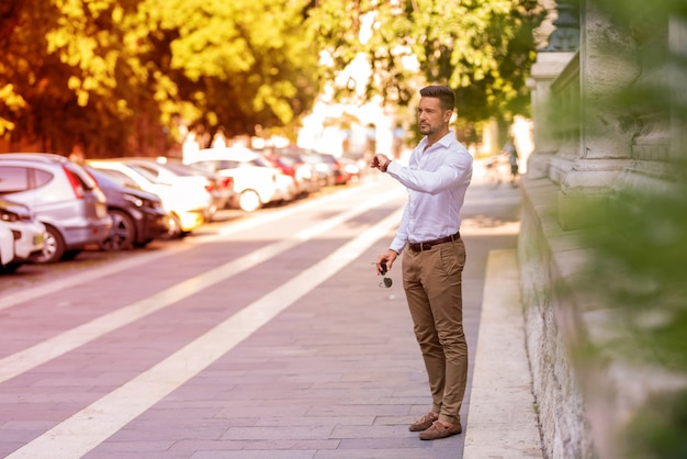 A young businessman standing and checking the time